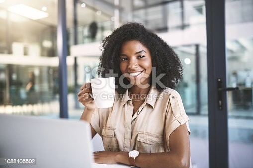 Portrait of a young businesswoman using a laptop and drinking coffee at her desk in a modern office