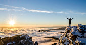 hiker enjoys success on top of a cliff above the sea of clouds. in front of him there is the rising sun spreading its warm beams over the land