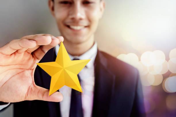 erfolg in geschäftlichen oder persönlichen talent konzept. glücklich kaufmann im schwarzen anzug lächeln auf den lippen und zeigt einen goldenen stern in der hand - belohnung stock-fotos und bilder