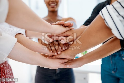 Cropped shot of a group of unrecognizable businesspeople joining hands together in a huddle inside an office
