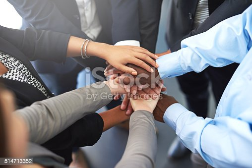 Cropped shot of a group of colleagues joining their hands in unity