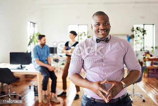 Portrait of a cheerful young businessman in an office with his colleagues in the background