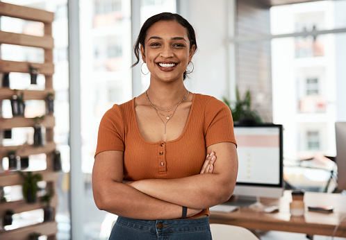 Portrait of an attractive and confident young businesswoman posing with her arms folded inside an office