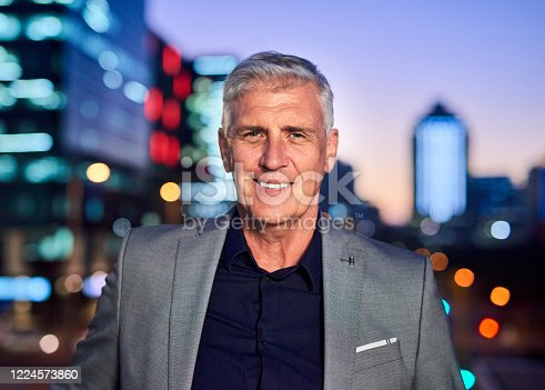 Portrait of a mature businessman posing outdoors in the city at night