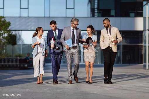 Five businesspeople walking and discussing some work paperwork