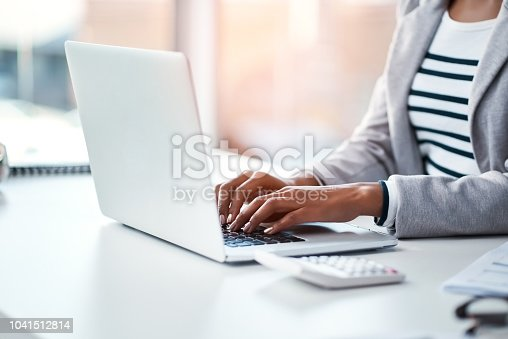 Cropped shot of a businesswoman using a laptop at her desk in a modern office