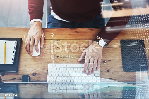 High angle shot of an unrecognizable businessman working on a computer in his office