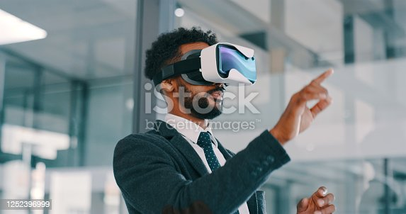 Shot of a young businessman using a virtual reality headset in a modern office