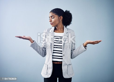 Studio shot of a young businesswoman gesturing with her hands against a grey background