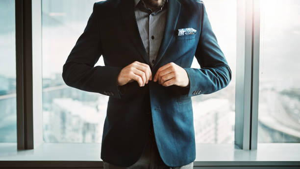 Success just got real Cropped shot of a stylish businessman button his jacket in a modern office blazer jacket stock pictures, royalty-free photos & images