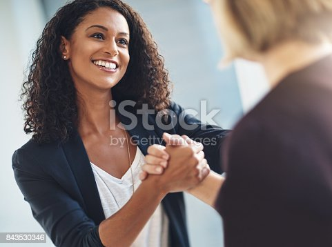 Shot of two businesswomen shaking hands in solidarity at work