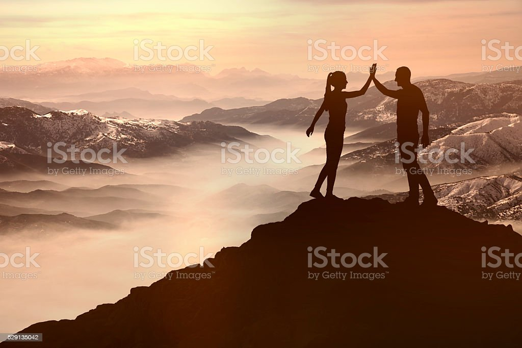 Success men and woman on the mountain stock photo