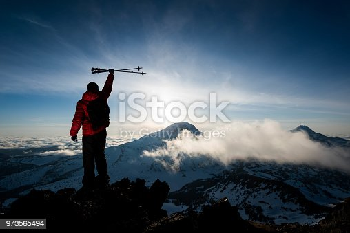 Man summiting the top of a mountain in the beautiful backcountry.