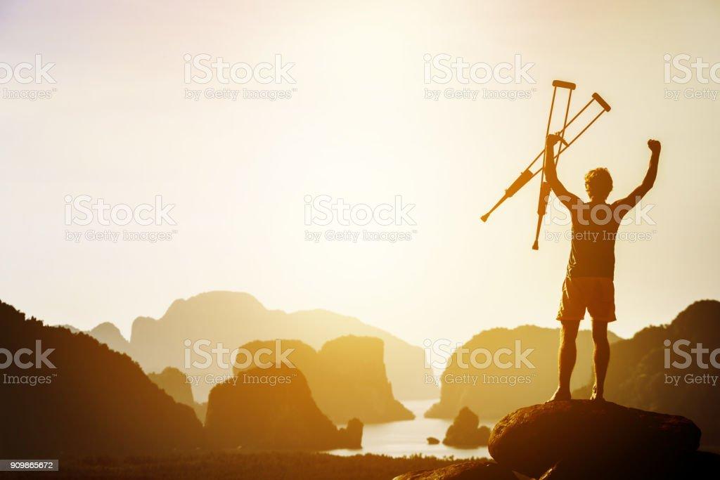 Concepto de éxito o ganador con hombre discapacitado y muletas - foto de stock