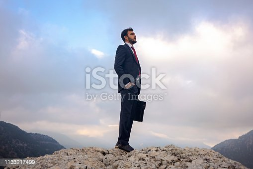 Young businessman on top mountain peak over clouds.