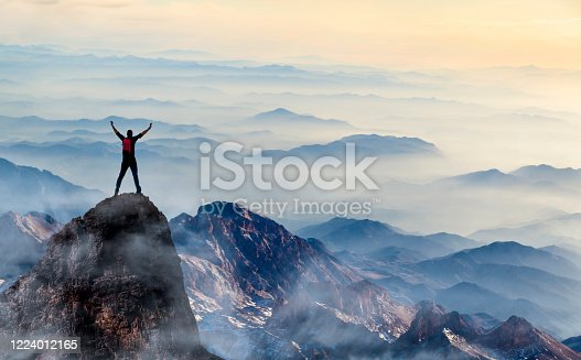 Young man enjoys success on top of a cliff