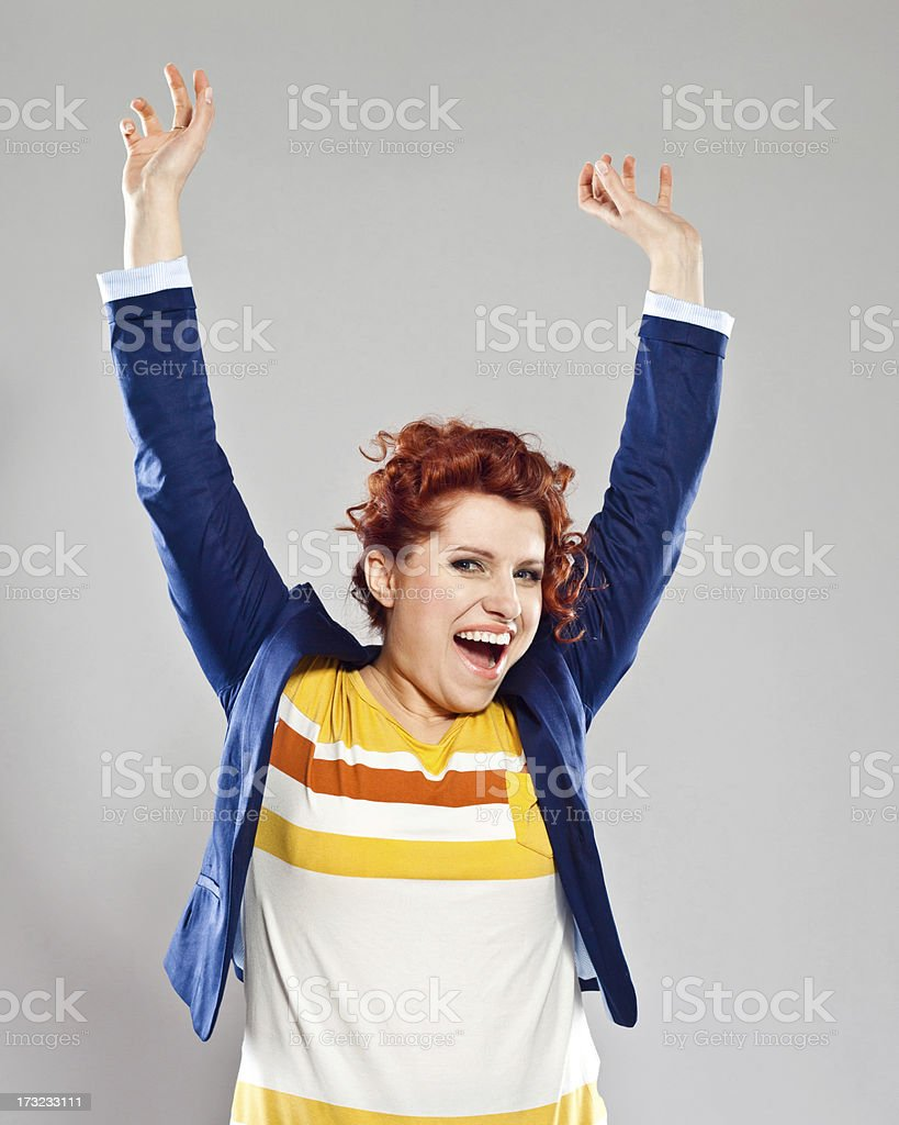 Success Portrait of happy young woman, raising her arms and laughing at camera. Studio shot, grey background. 25-29 Years Stock Photo