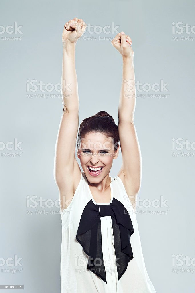 Success Portrait of attractive young woman raising her fists and laughing at the camera. Studio shot. 20-24 Years Stock Photo