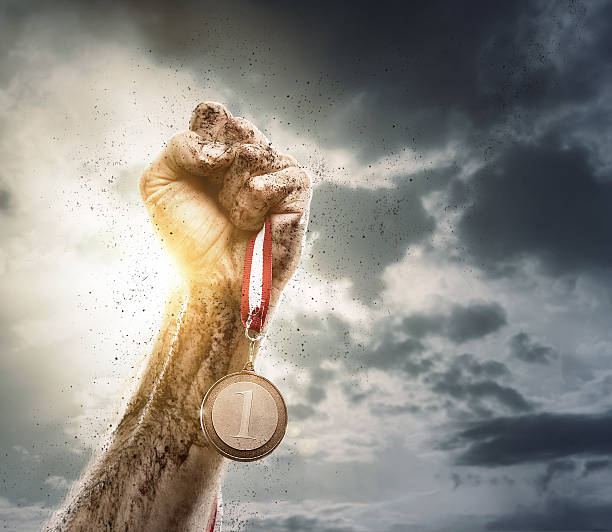 Success Male hand rise up a gold medal against the dramatic sky with copy space medal stock pictures, royalty-free photos & images