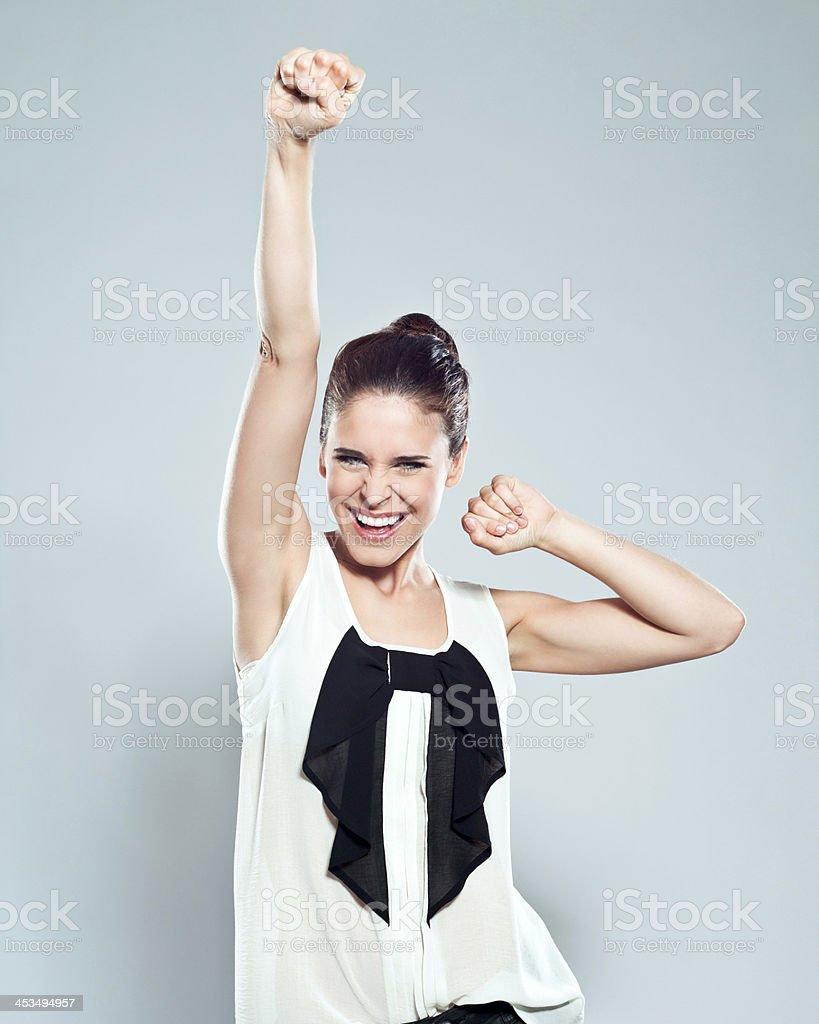 Success Portrait of attractive young woman raising her fists and laughing at the camera. Studio shot on a grey background. 20-24 Years Stock Photo