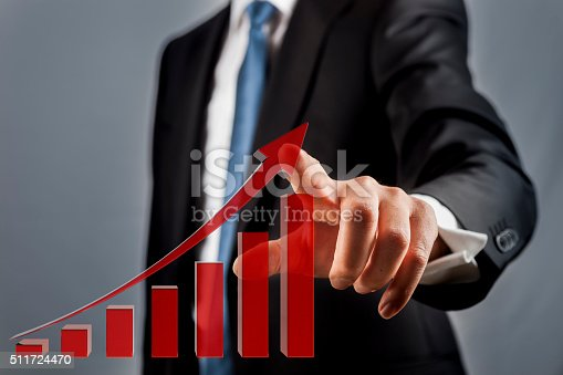 Businessman using a touch screen displaying a growth chart
