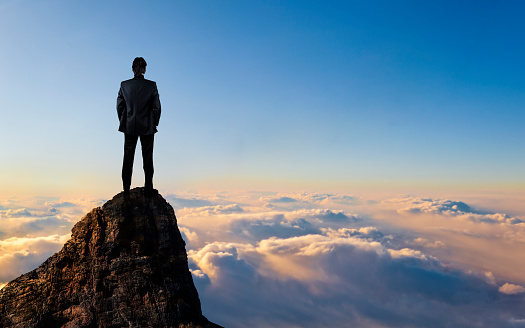 Young Businessman enjoys success on top of a cliff above the sea of clouds.