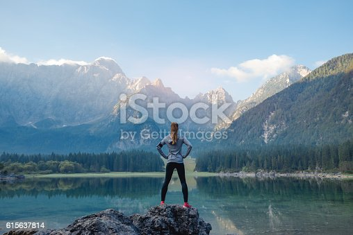 Woman standing on the rock. Success concept.