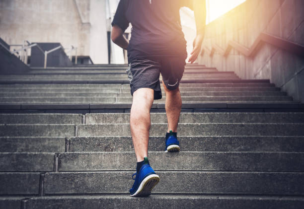 Success Close up of young man running up the stairs with running clothes stepping stock pictures, royalty-free photos & images