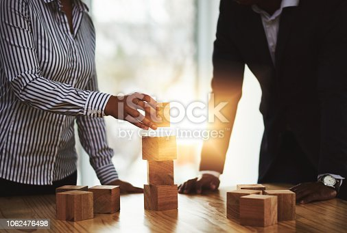 Shot of two businesspeople stacking wooden blocks together in an office