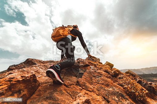 istock Success woman hiker hiking on sunrise mountain peak - Young woman with backpack rise to the mountain top. Discovery Travel Destination Concept 1285296688