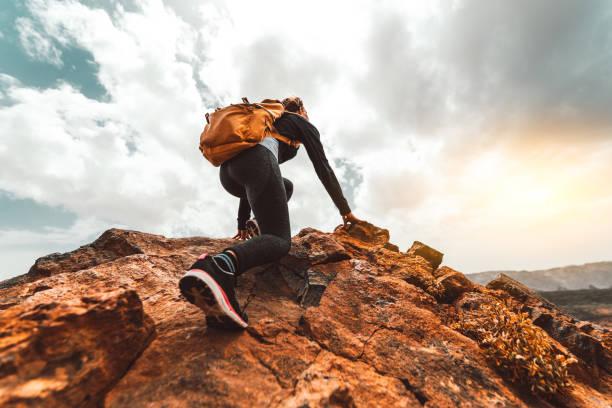 success mujer senderismo senderismo en el pico de la montaña del amanecer - mujer joven con mochila subir a la cima de la montaña. concepto de destino de viaje discovery - excursionismo fotografías e imágenes de stock