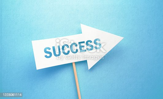 istock Success Written White Arrow On Blue Background 1223061114