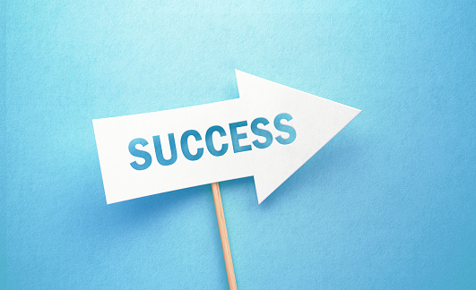 Success written white arrow on blue background. Horizontal composition with copy space. Success concept.