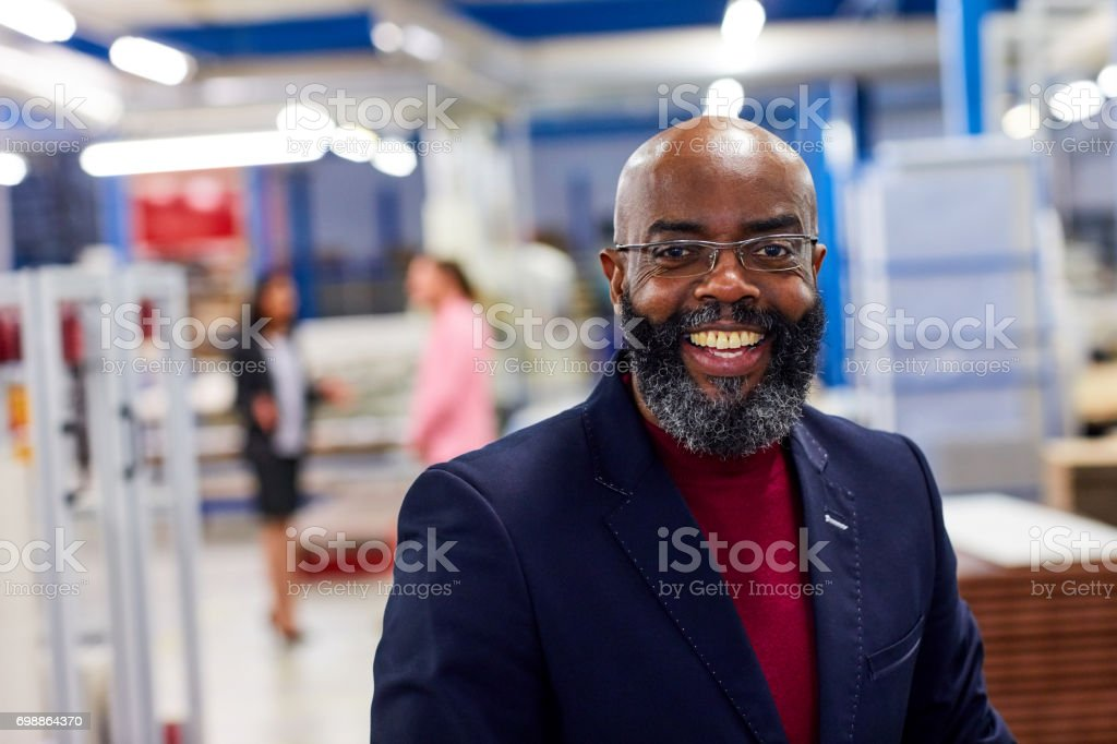 Successful african businessman standing in factory stock photo