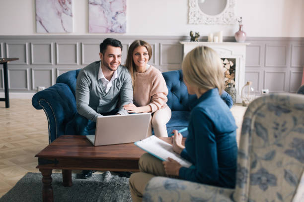 Successful agent giving consultation to family couple about buying house. stock photo