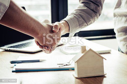 istock Successful agreement , estate,home buying contract concept, buyer shaking hand with bank empoyees after finishing signing contract in office 922210350
