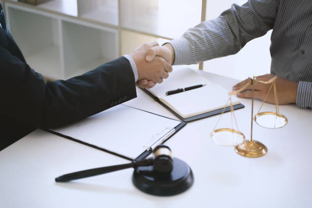 Successful agreement, Justice lawyer hand shaking with Client in courtroom. stock photo