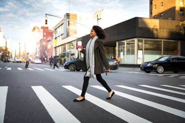 succesvolle en elegante vrouw loopt de straten van new york - oversteken stockfoto's en -beelden