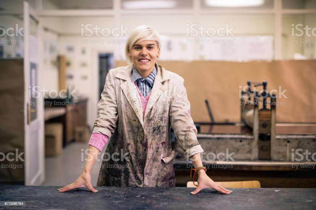 Successful and proud young woman standing in her working uniform in atelier stock photo