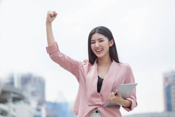 Successful asian business woman arms up celebrating with tablet computer in hand in city outdoors . girl excited winner.Cheerful ,happy, female checking online good news stock photo
