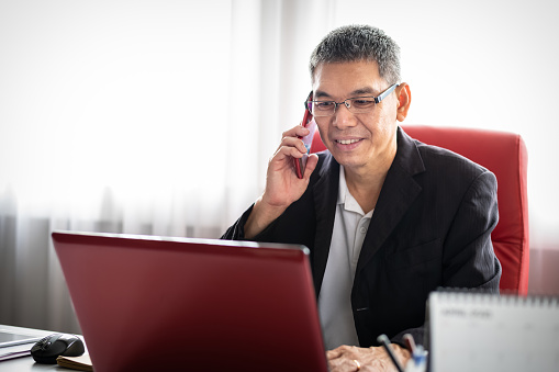 Mid aged Asian entrepreneur communicating over smart phone while working on laptop in the office. 5G & Wireless Technology, Finance & Economy, Business ownership & Entrepreneurship Concepts.