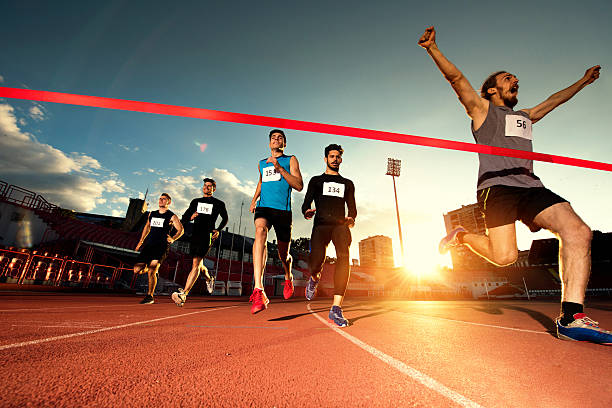 successful athlete crossing the finish line and winning the race. - marathon stock photos and pictures