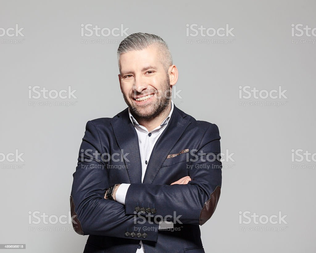 Successful bearded grey hair businessman Portrait of elegant bearded grey hair businessman standing against grey background with arms crossed and smiling at camera. Studio shot, one person.  2015 Stock Photo