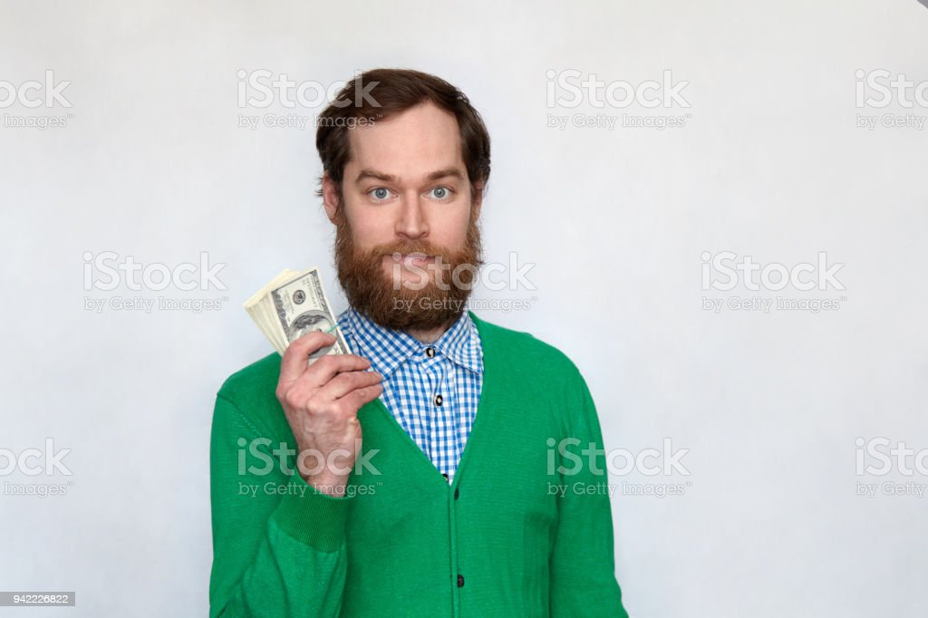 Successful bearded man holding a bundle of money stock photo