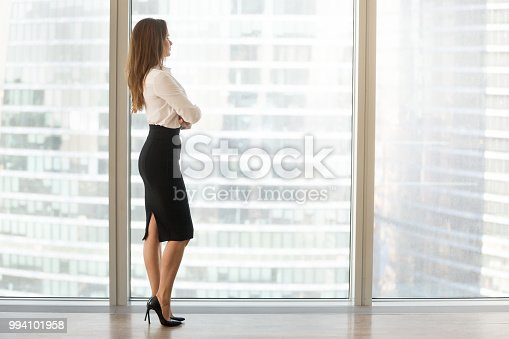 Successful businesswoman standing looking out of window enjoying city view and contemplating, confident rich woman leader thinking of business success and future vision planning new goals, copy space