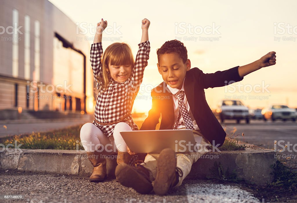 Successful business children using laptop at sunset. - foto de stock