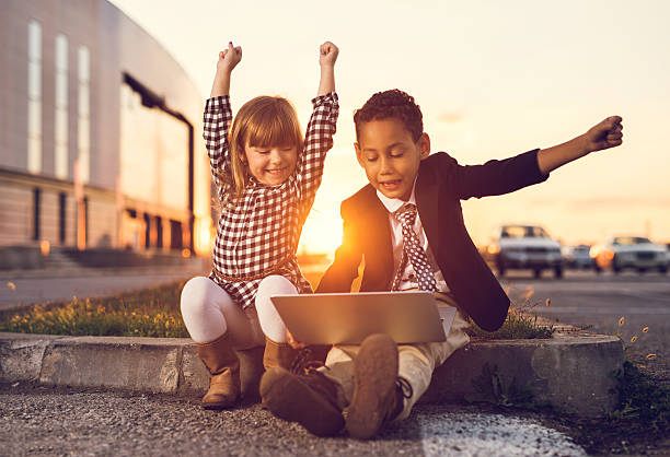 Successful business children using laptop at sunset. stock photo