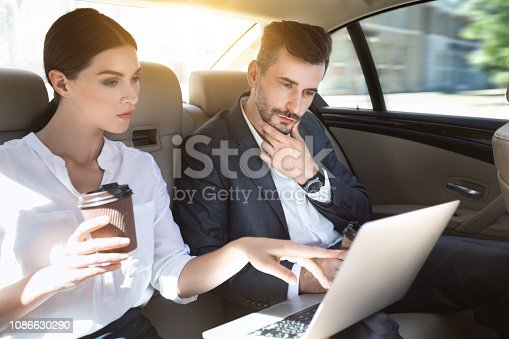 istock Successful business couple working together in car 1086630290