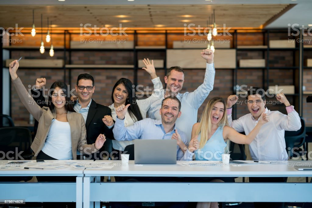 Successful business group celebrating an achievement at the office stock photo