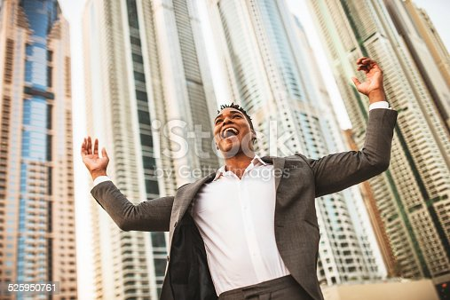 1012628232istockphoto Successful business man against the skyscraper 525950761